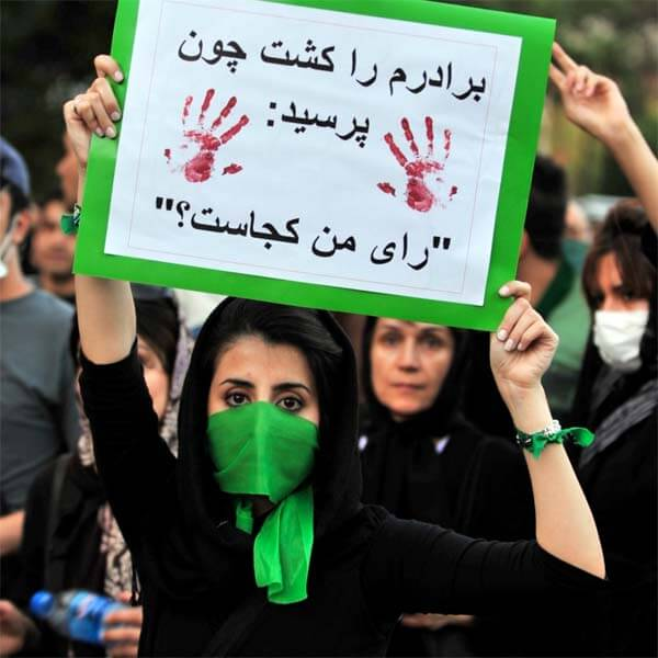 "A protester on the streets of Iran, June 17, 2009. The sign reads ""They Killed My Bro Koz He Asked ""Where's My Vote."" Creative Commons photo by Hamed Saber."