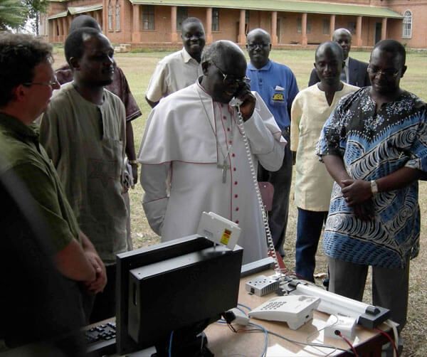 In 2007, Ugandan Archbishop Odama places an internet phone call to an internally-displaced people's camp 70 km away. Internet technologies are encouraging ground-up development like this across the continent. Photo courtesy Bosco-Uganda.