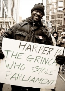 Protestor at a Toronto rally carrying a sign reading: Harper is the Grinch who stole Parliament. Creative Commons photo by Fifth Business.