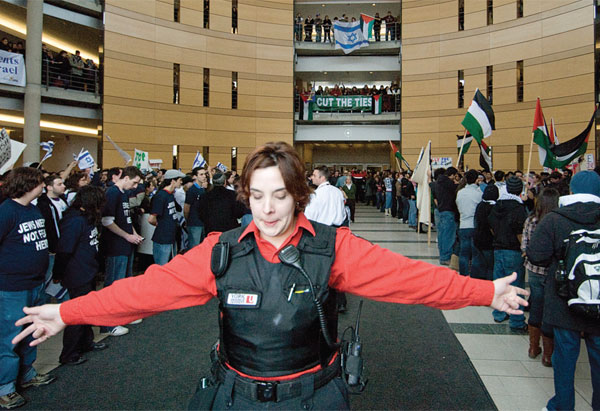 A security guard separates pro-Palestine and pro-Israel groups during York University's Israeli Apartheid Week in February 2009. Photo by Jad yaghmour (Excalibur).