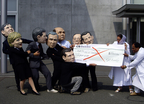 Costumed activists pretend to revoke aid cheque