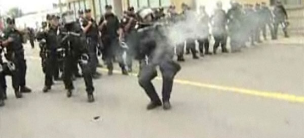 riot police shooting tear gas canister