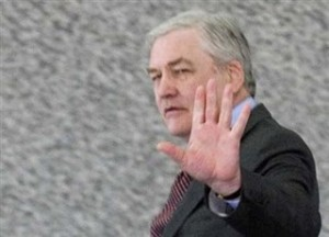Conrad Black stands in front of granite wall with one hand up. Copyright bildungblog.blotspot.com 2010