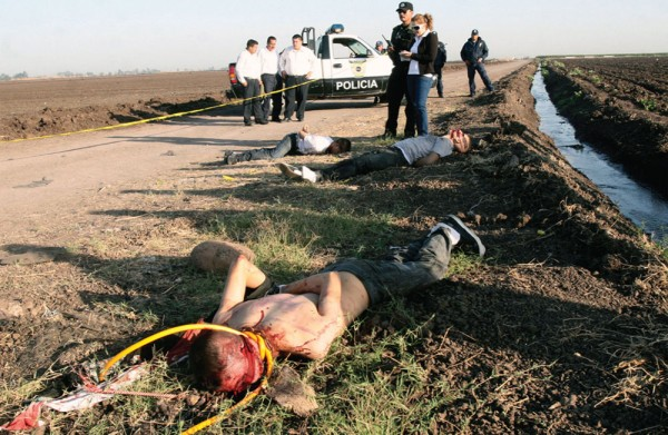 Bodies lie in a ditch in rural Mexico, as police look on. Photo by Tomas Bravo/Reuters