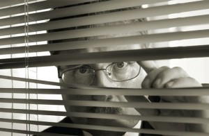 Suspicious man peering through blinds